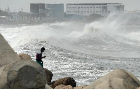 A man looks out as waves hit a breakwater at Kasimedu fishing harbour in Chennai on May 19, 2020, as Cyclone Amphan barrels towards India's eastern coast. - Millions of people were being moved to safety on May 19 as one of the fiercest cyclones in decades barrelled towards India and Bangladesh, with evacuation plans complicated by coronavirus precautions. Both countries are under various stages of lockdown because of the disease, with infections still surging. (Photo by Arun SANKAR / AFP) (Photo by ARUN SANKAR/AFP via Getty Images)