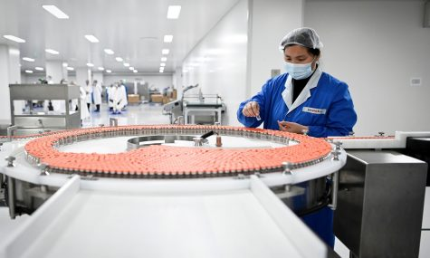 (FILES) This file photo taken on September 24, 2020 shows a staff member working during a media tour of a new factory built to produce a COVID-19 coronavirus vaccine at Sinovac, one of 11 Chinese companies approved to carry out clinical trials of potential coronavirus vaccines, in Beijing. - With the rollout of coronavirus vaccines beginning across the world, China has positioned itself as a key player, promising poorer nations priority access to its jabs. (Photo by WANG Zhao / AFP) / TO GO WITH China-vaccines-virus-health-diplomacy-politics,FOCUS by Helen ROXBURGH and Poornima WEERASEKARA